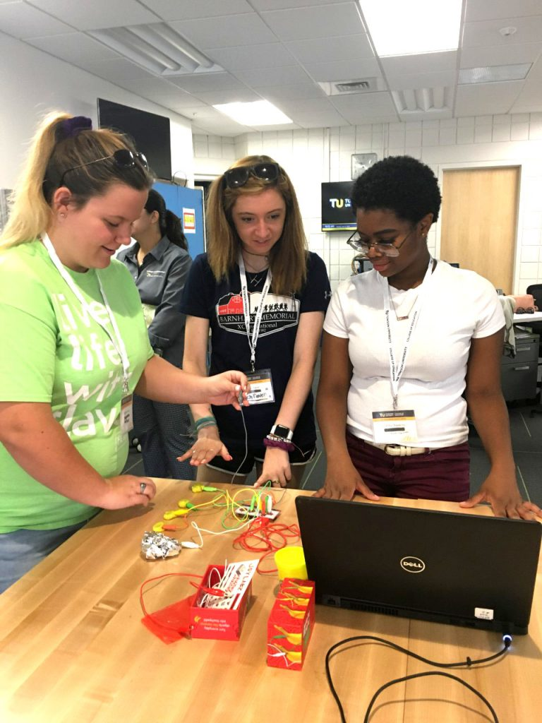 Three students gathered in the College of Educations new makerspace which they call sandbox